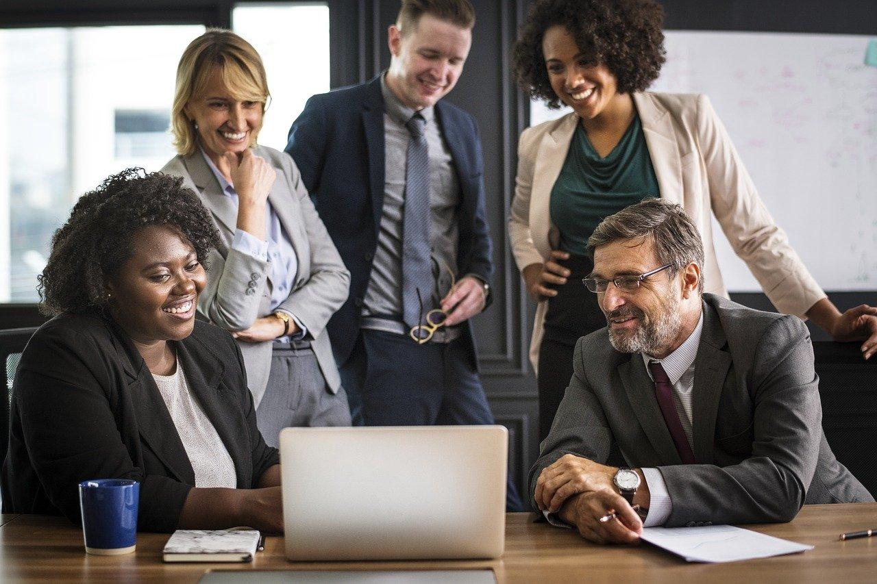 Zwei Mitarbeiter sitzen, drei Mitarbeiter stehen und schauen auf einen Laptop-Bildschirm und diskutieren angeregt.